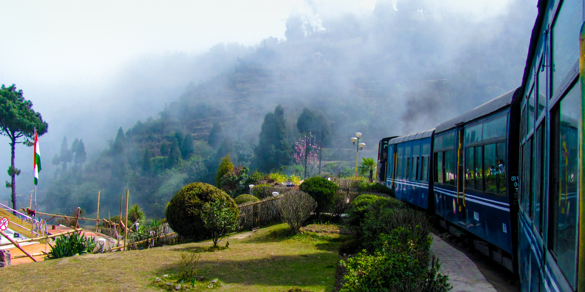 Train passing a beautiful garden and entering into fog at Darjeeling, India